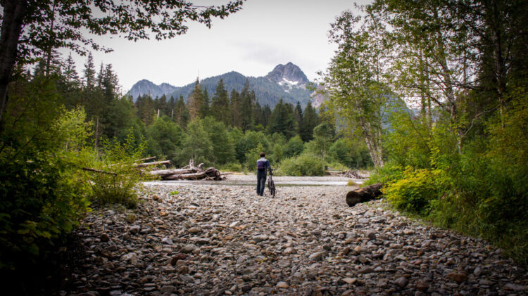 Man with a mountain bike walking towards a mountain in the distance, on a rocky path, preparing to cross a stream.