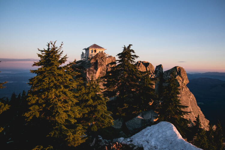 Fire lookout on the top of Mt Pilchuck seen at sunrise, surrounded by green tres, rocky cliffs, and a bit of snowpack on the mountain.