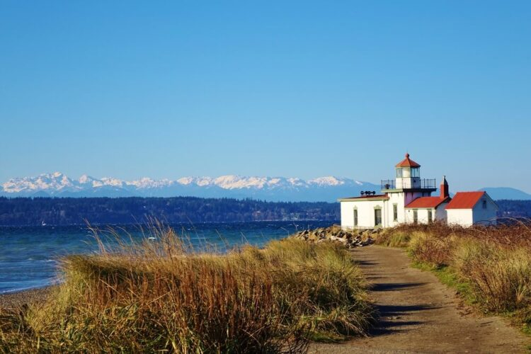 A grassy path leading to a lighthouse in Seattle on the water with mountains in the background.