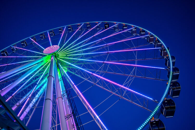 A low-angle shot looking up at the neon pink, blue, and green lights of the Great Wheel (Ferris Wheel) in Seattle.