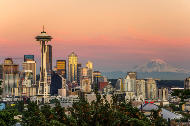 An orange and pink sunset seen from Kerry Park with the Space Needle and Mt Rainier covered in snow off in the distance.