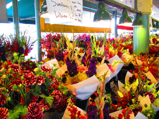 Brilliant red, purple, and green floral bouquets at a flower stall in Pike Place Market, a popular Seattle date location.