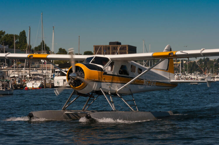 A yellow and white seaplane landing on the water on two small pontoons