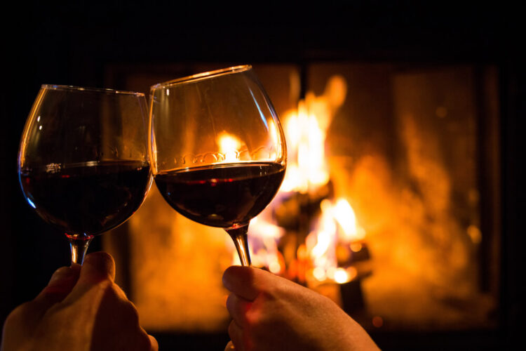 two glasses of wine in front of a fire place