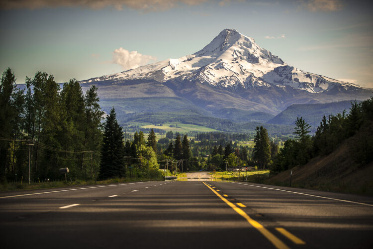 empty highway as seen on one of the best road trips in oregon with mt hood in the background