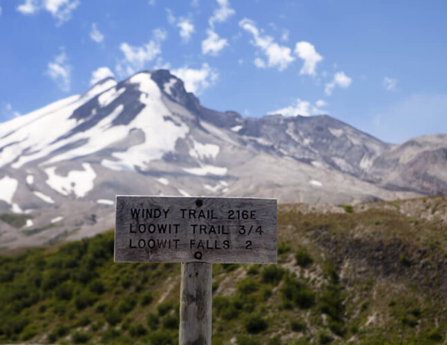 "Sign which reads ""Windy trail 216E, Loowit Trail 3/4, Loowit Falls 2"" in front of a partly snow-covered Mt St Helens hike"