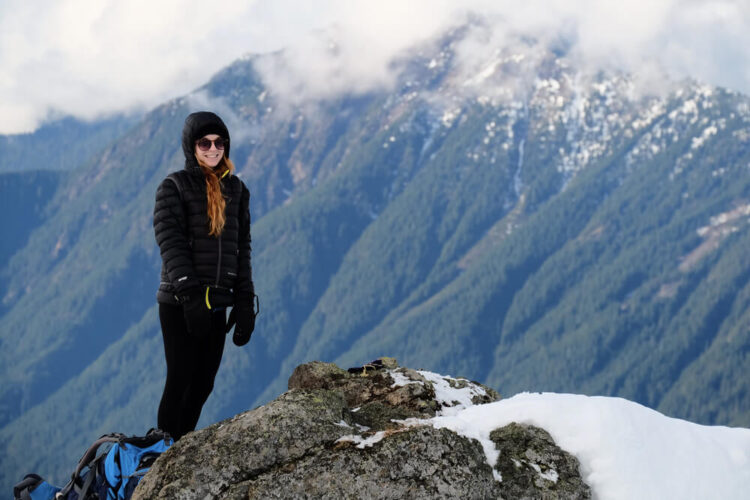 Woman at the peak of Mt Dickerman wearing black athletic winter clothes and a blue backpack at her feet, next to some snowpack on the mountain, with green mountains in the distance.