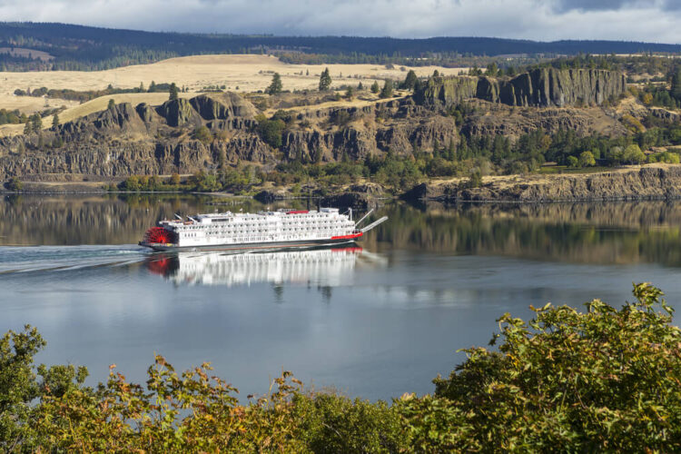 An old fashioned paddle boat (white boat with red paddle) going on the Columbia River