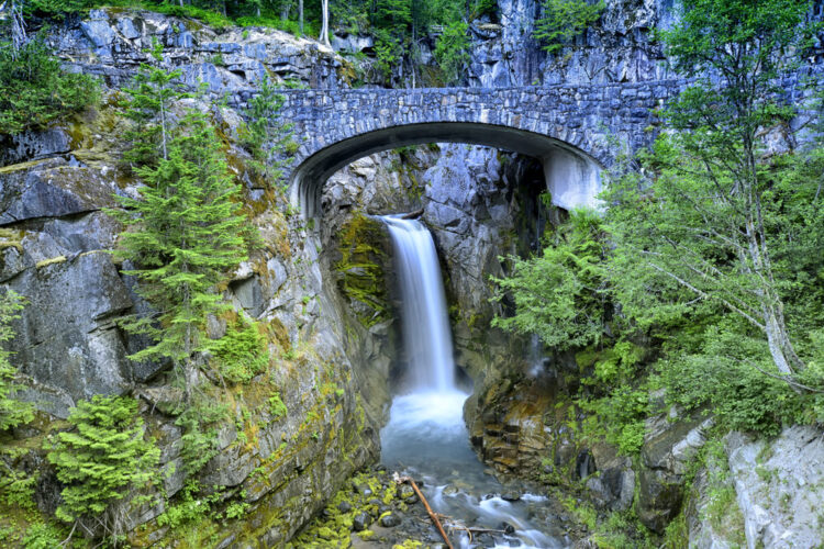 A beautiful single drop waterfall in Mt Rainier National Park, with a stone bridge in front of the waterfall, and trees around it.