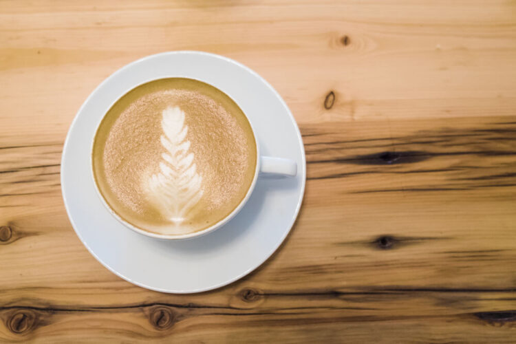 A perfect cup of coffee with latte art on a wooden table.