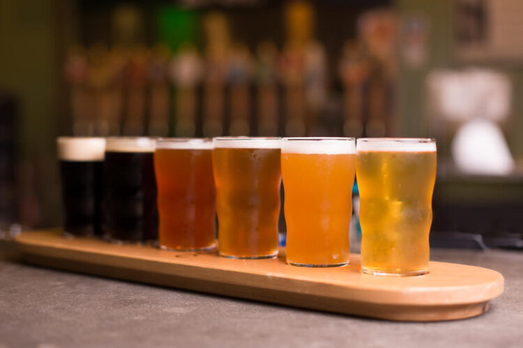 Flight of six beers ranging from dark stouts to red ales to lagers, served on  a plank of wood at a brewery.