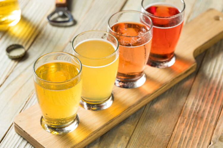 Flight of four ciders, ranging from a light golden color to a deep almost red color.