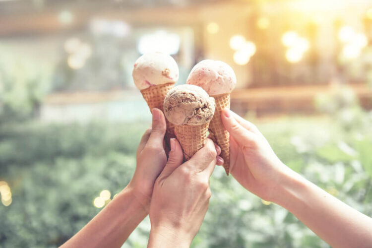Three ice creams being held together in soft light with a park as the background.