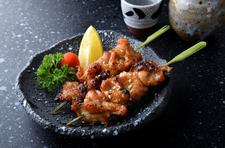 Two sticks of Japanese yakitori (grilled chicken skewers) served on a plate.