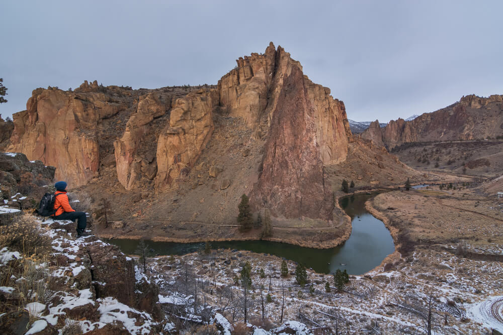 Person sitting in Smith Rock State Park looking at the landscape and river
