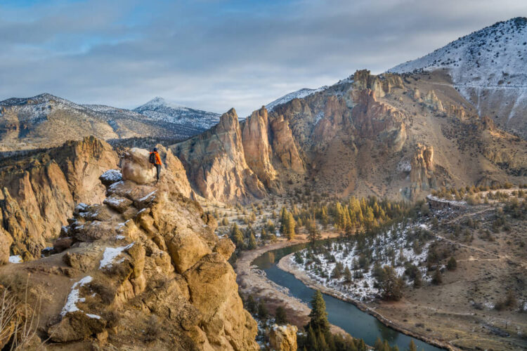 Hiker in a red shirt and black pants with a backpack on, looking over the landscape in Smith Rock, Oregon over a river with a light dusting of snow.