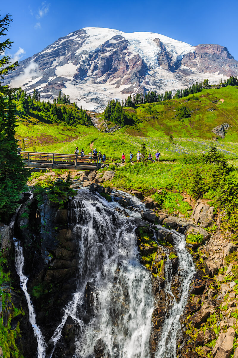 A group of hikers crossing a bridge, which spans over a narrow but long waterfall in Mt Rainier National Park, with a snow-capped mountain behind it.