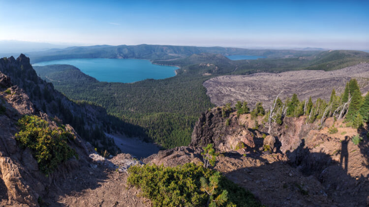Newberry Caldera area from Paulina Peak, view of a deep turquoise lake far in the distance surrounded by trees and desert looking landscape.