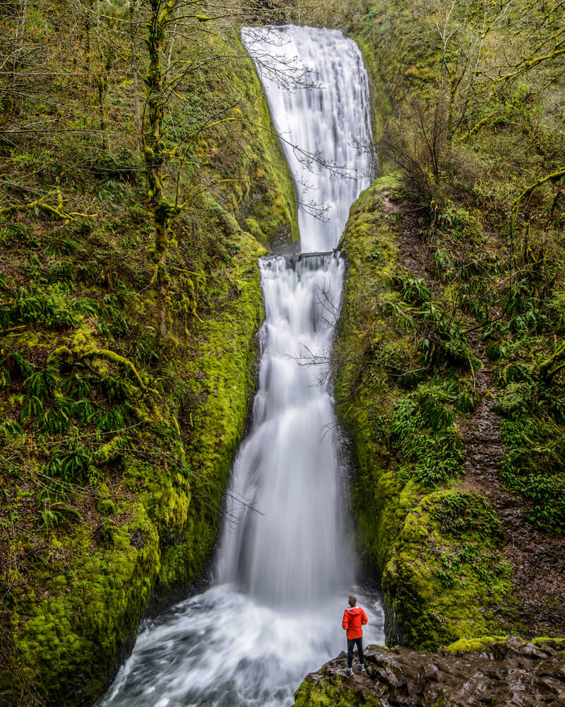 A man in a red jacket standing at an outlook point in front of the multi-tiered Bridal Veil Fall, one of the most famous waterfalls near Seattle
