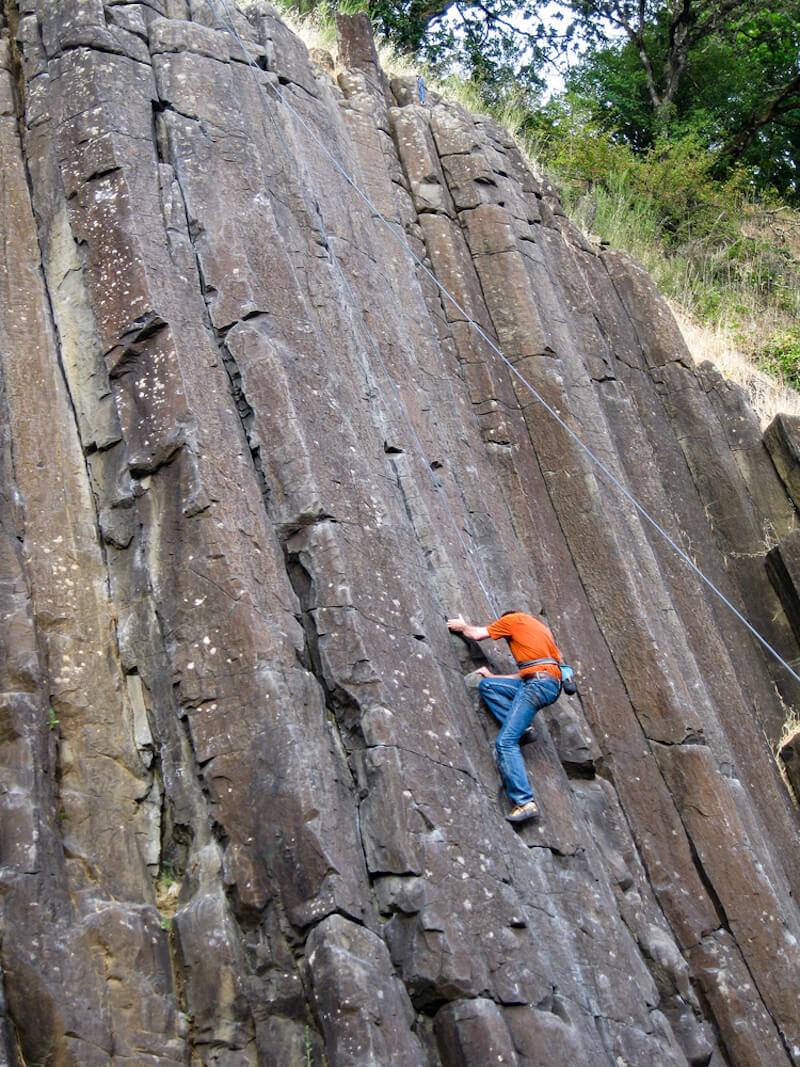 Man in orange shirt and jeans trying to climb up the basalt columns at Skinner Butte, a popular outdoorsy thing to do in Eugene Oregon