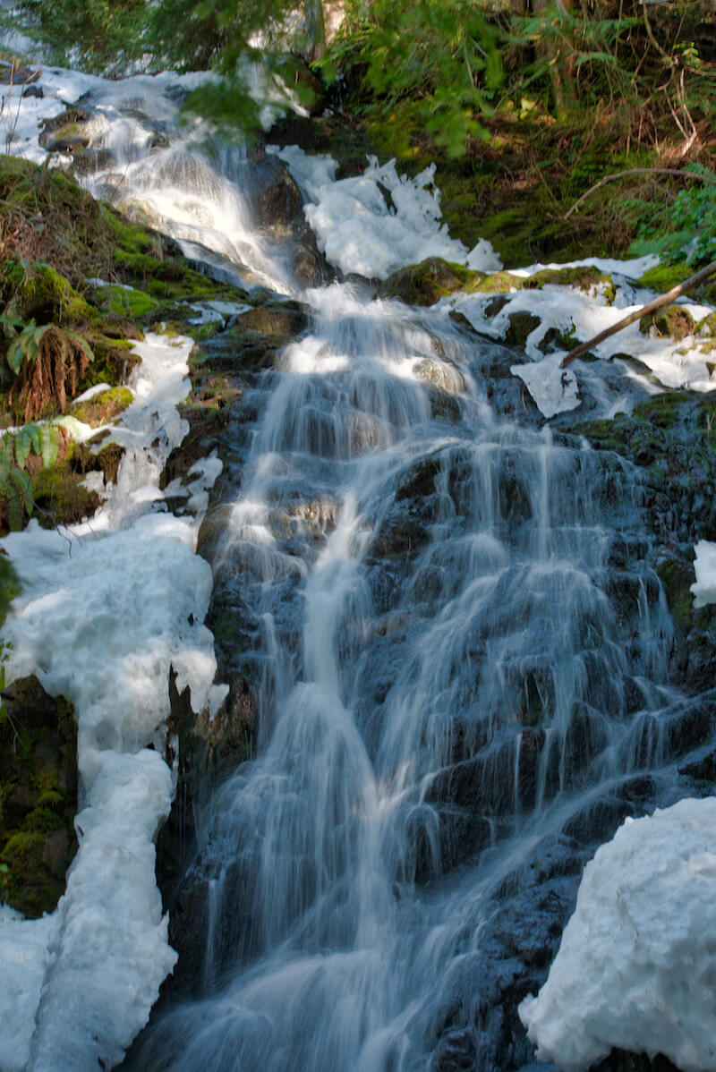Melted snow on each side of the waterfall, which is flowing over rocks, not far from Seattle but requiring a hike to reach it.