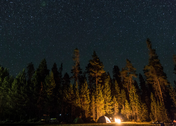 People camping in a tent with stars above them.