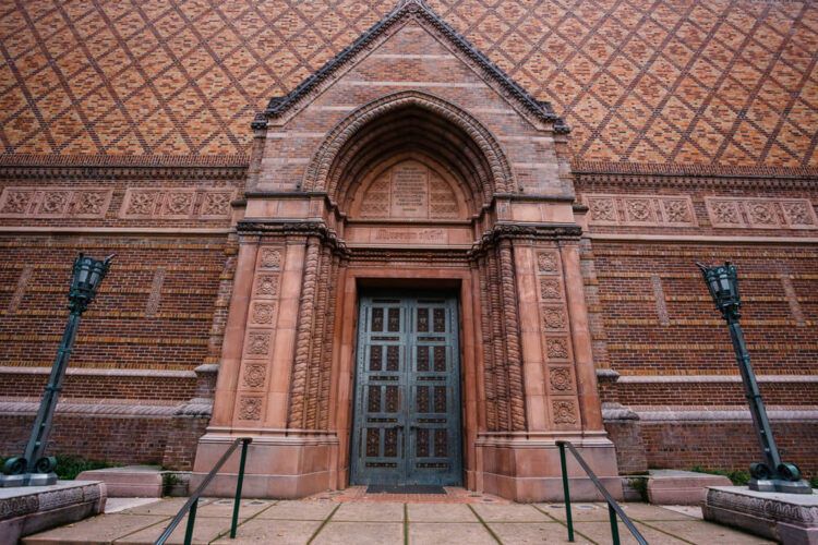 Brick red building with carving and two vintage looking lamposts with an elaborate door. Building is the University of Oregon Jordan Schnitzer Museum of Art building exterior on the Eugene Campus.