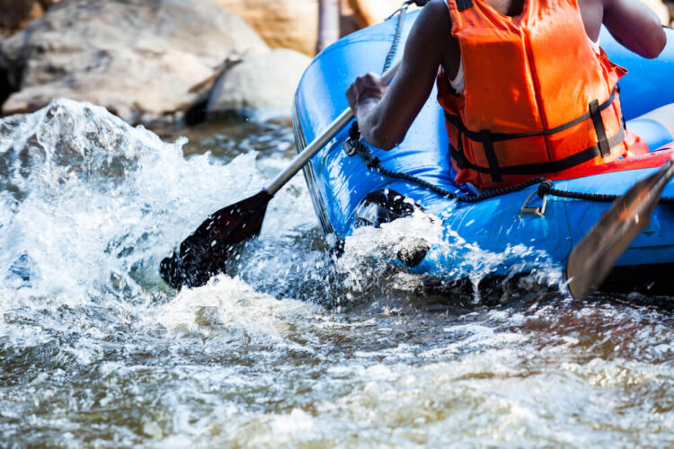 Black man in a orange vest in a blue raft going down white water rapids