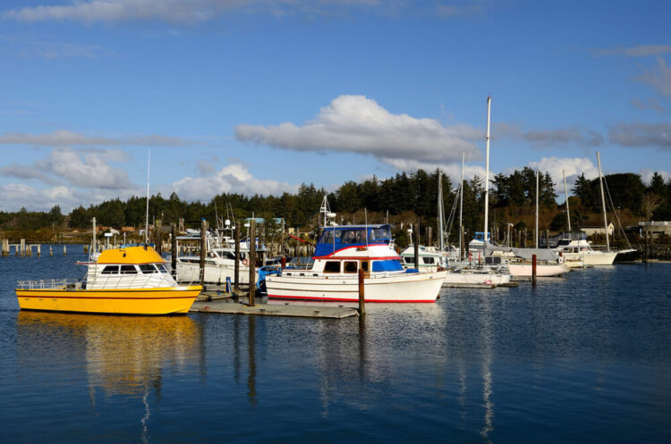 Small fishing boats parked in the Coquille River marina, in Bandon Oregon, white and yellow boats in the marina