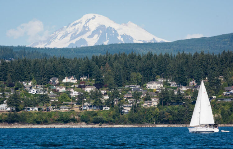 A photo of Mount Baker with a sailboat and houses in the Bellingham town area on the water, a beautiful coastal city in Washington.