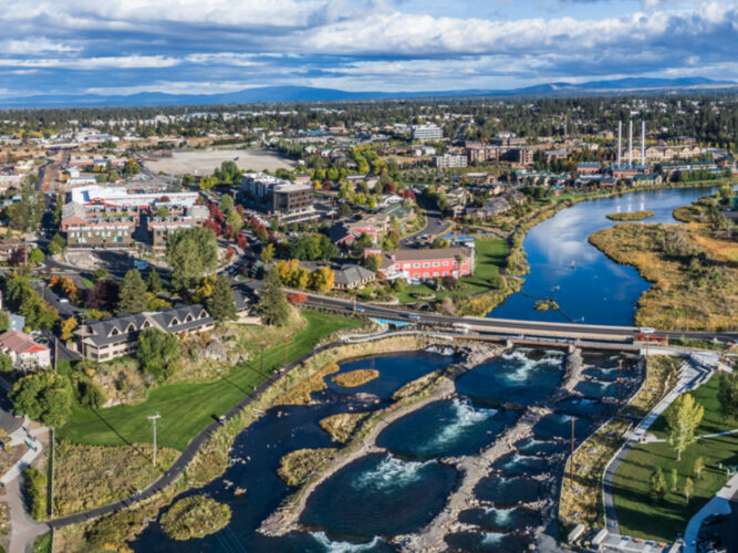An aerial view of Bend Oregon with the white water river and buildings on the edge of the river banks