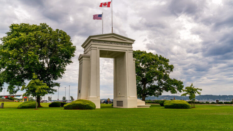 US Peace Arch border crossing. Canadian and US flags are waving in the wind on a beautiful cloudy sky.