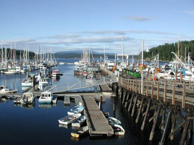 Wooden pier with many small boats and sailboats in the marina at Friday Harbor in Washington's San Juan Island.