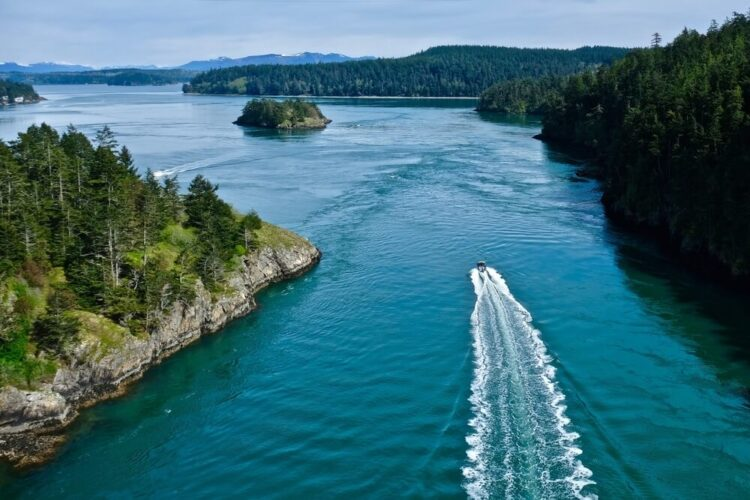 Boat in the ocean leaving a wake behind it, among islands with views of Deception Pass State Park in the Puget Sound.