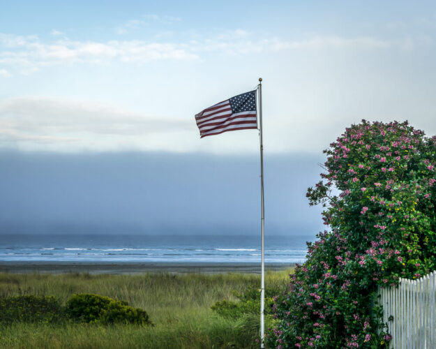 American flag waving in the wind surrounded by green grass and beach coastline with a white picket fence and pink flowers on the right of the photo.