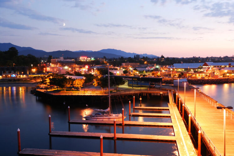 Night scene at Port Angeles in Washington state, lights on in the harbor marina with sunset views in the distance.