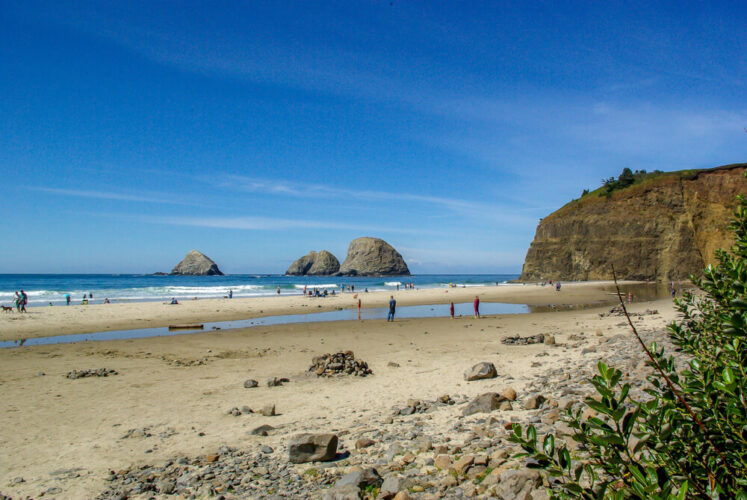 People on Rockaway Beach, with three large sea stacks, on a gorgeous sunny day on the Oregon coast, a short road trip from Portland.