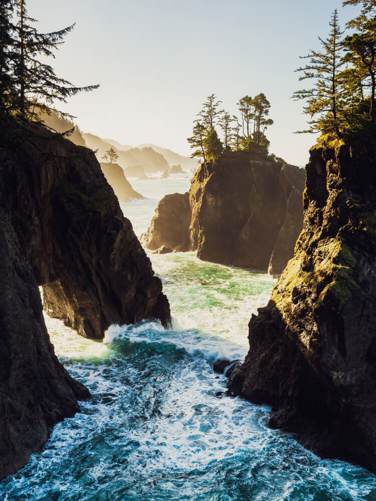 vertical image showing the sea stacks of the oregon coast at sunrise with warm light bathing the rock formations