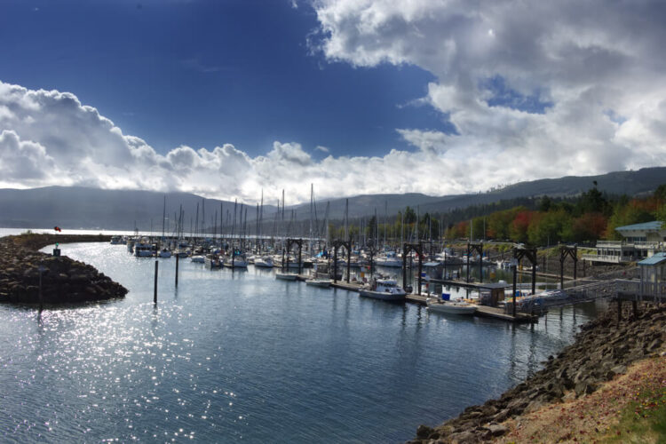 Boats in the marina of Sequim in the fall with some fall foliage in the trees in the distant background and a partly cloudy sky.