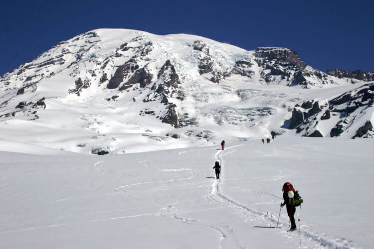 people hiking through the snow during winter at mount rainier