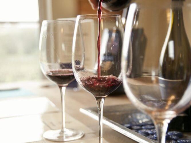 row of three wine glasses being filled with tastes of red wine from oregon