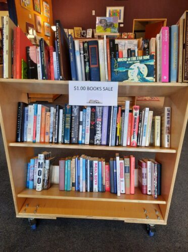 sign that reads $1 used books sale with a shelf of books