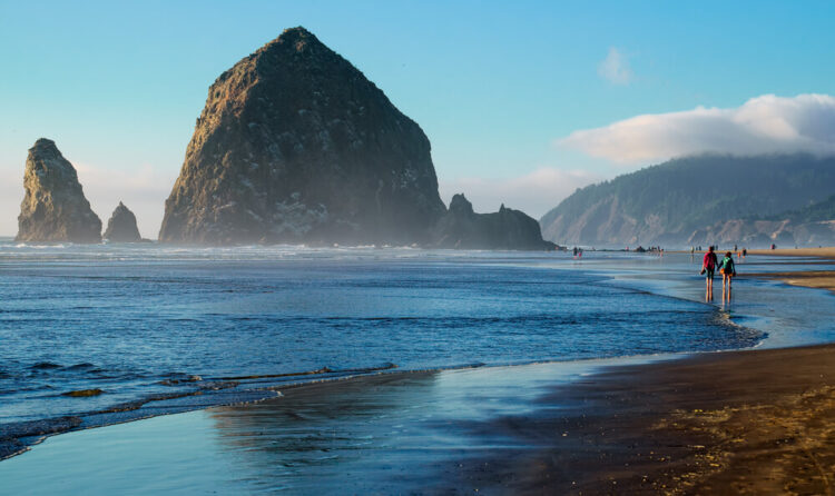 the giant looming haystack rock, walking here is one of the coolest things to do in cannon beach oregon