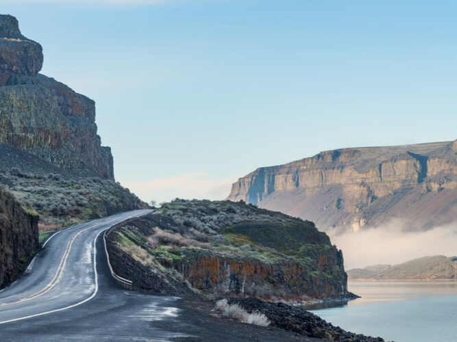 Driving on the edge of a lake or river along the Coulee Corridor while on a washington state road trip