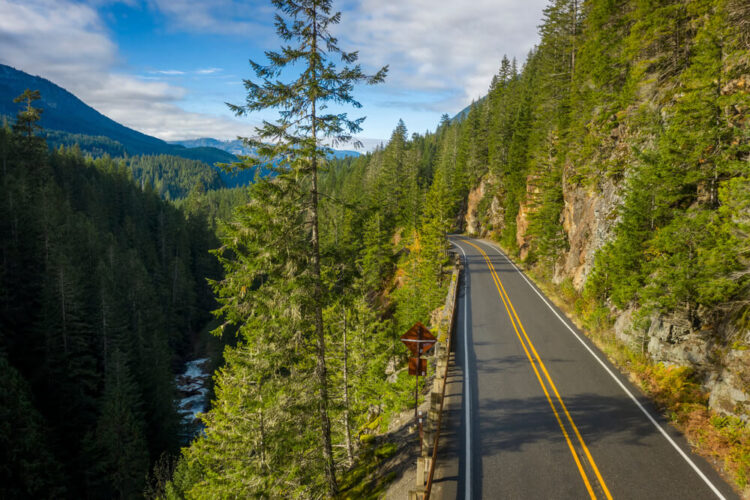 The scenic road of the Mt Baker Highway against pine trees and a river on one edge of the drive