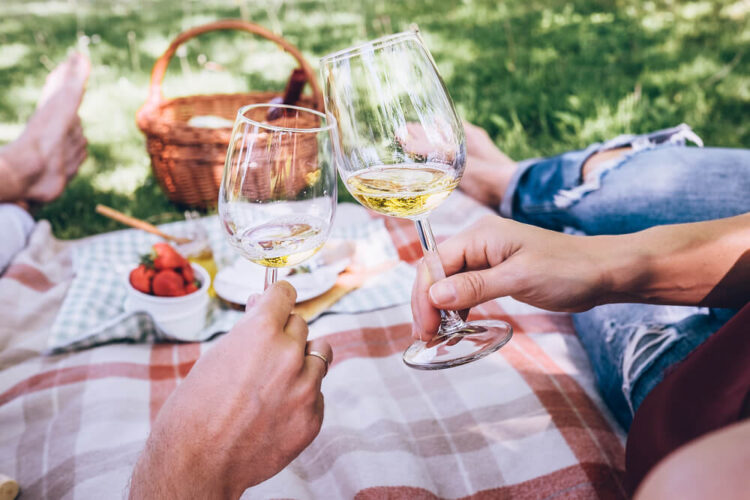 Hands cheersing with white wine while enjoying a picnic