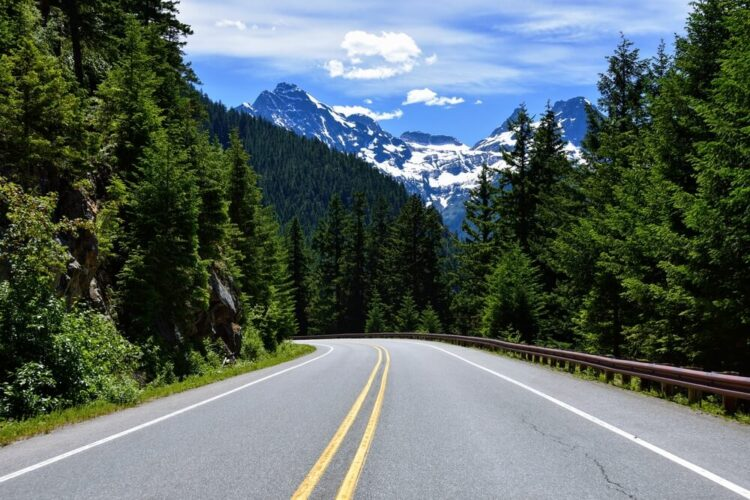 Hitting the open road on a two lane highway while driving in Washington state with snow-capped mountains in the distance.