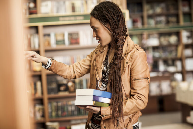 African American woman with braids picking books at a bookstore