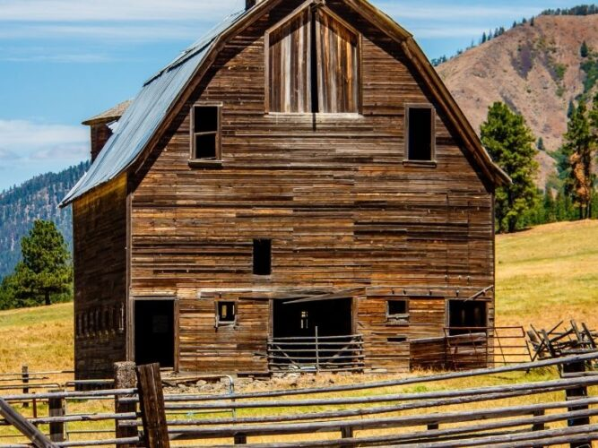 a small barn in the cle elum area of washington with a yellow-grassy field and fence