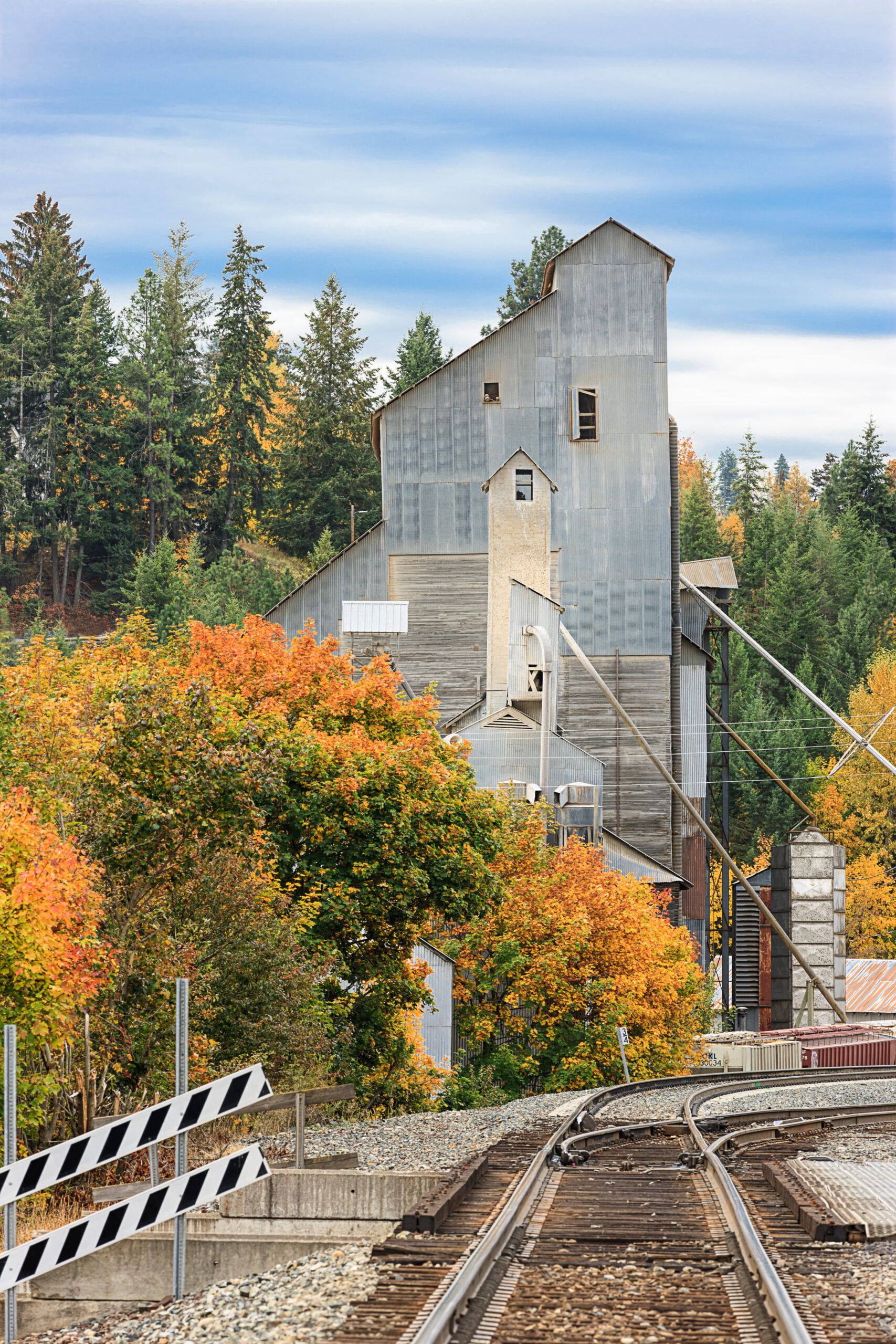 a cute barn-like structure in the small town of bonners ferry idaho, with a railroad track and orange fall foliage